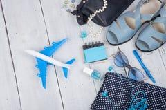 μπλε τσάντα, γυαλιά ηλίου, σανδάλια, στιλβωτική ουσία καρφιών, σημειωματάριο ακουστικών και λίγο αεροπλάνο στο άσπρο ξύλινο υπόβα Στοκ Φωτογραφίες