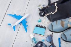 μπλε τσάντα, γυαλιά ηλίου, σανδάλια, στιλβωτική ουσία καρφιών, σημειωματάριο ακουστικών και λίγο αεροπλάνο στο άσπρο ξύλινο υπόβα Στοκ Εικόνες