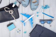 μπλε τσάντα, γυαλιά ηλίου, σανδάλια, στιλβωτική ουσία καρφιών, σημειωματάριο ακουστικών και λίγο αεροπλάνο στο άσπρο ξύλινο υπόβα Στοκ φωτογραφία με δικαίωμα ελεύθερης χρήσης