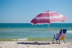 Μπλε τσάντα καρεκλών παραλιών και υπαίθρια ομπρέλα μέχρι το καλοκαίρι κυμάτων μπλε ουρανού θάλασσας Στοκ Φωτογραφία