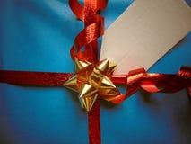 Μπλε τυλιγμένο δώρο με την κενή ετικέττα και την αρκετά λαμπρή κορδέλλα Στοκ φωτογραφία με δικαίωμα ελεύθερης χρήσης