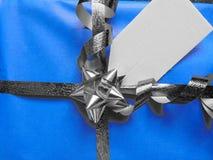 Μπλε τυλιγμένο δώρο με την κενή ετικέττα και την αρκετά λαμπρή κορδέλλα Στοκ εικόνα με δικαίωμα ελεύθερης χρήσης