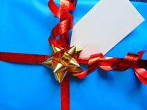 Μπλε τυλιγμένο δώρο με την κενή ετικέττα και την αρκετά λαμπρή κορδέλλα Στοκ εικόνες με δικαίωμα ελεύθερης χρήσης