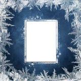 Μπλε υπόβαθρο Χριστουγέννων με τα παγωμένα σχέδια και κάρτα για το κείμενο ή τη φωτογραφία Στοκ εικόνα με δικαίωμα ελεύθερης χρήσης