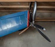 Μπλε φτερό αεροπλάνων των πρότυπων αεροσκαφών με την ένωση προωστήρων σε ένα ξύλινο ράφι του οχήματος spung Έλικας και μπλε Στοκ εικόνα με δικαίωμα ελεύθερης χρήσης