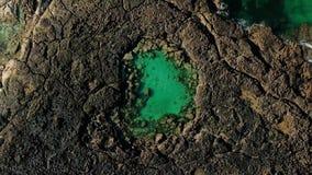 Μπλε φυσική πισίνα στη μέση των μαύρων vulcanic βράχων - πράσινο ωκεάνιο νερό λιμνοθαλασσών - εναέρια τοπ άποψη - ομορφιά του πλα απόθεμα βίντεο