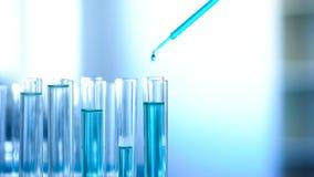 Μπλε χημικό υγρό που στάζει στους σωλήνες εργαστηρίων, εξεταστικό πείραμα προϊόντων καθαρισμού στοκ εικόνες
