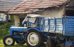 Μπλε χώρος στάθμευσης τρακτέρ στο προαύλιο του παλαιού, ηλικίας σπιτιού Επαν στοκ εικόνες