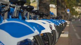 Μπλε eco-ποδήλατα που στέκονται στη σειρά στην οδό, ποδήλατα για τη μίσθωση, αστική μεταφορά φιλμ μικρού μήκους