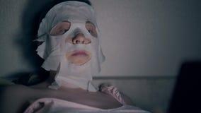 Μπλε eyed brunette στην άσπρη αναζωογονώντας μάσκα φύλλων απόθεμα βίντεο