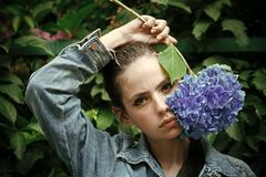 Μπλε hydrangea λαβής γυναικών στο πρόσωπο makeup Στοκ Φωτογραφίες