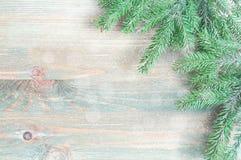 μπλε snowflakes ανασκόπησης άσπρος χειμώνας Πράσινοι κλάδοι δέντρων έλατου με χειμερινά snowflakes στο ξύλινο υπόβαθρο Στοκ Εικόνες