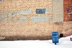 Μπλε trashcan στο χιόνι στο παλαιό τούβλινο σκηνικό τοίχων στοκ εικόνες με δικαίωμα ελεύθερης χρήσης
