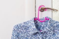 Μπλούζα στην κρεμάστρα στη λαβή πορτών Στοκ Φωτογραφίες