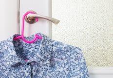 Μπλούζα στην κρεμάστρα στη λαβή πορτών Στοκ Φωτογραφία