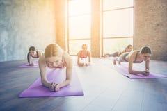 Μπορούμε να το κάνουμε! Άσκηση σανίδων ABS Πέντε συγκεντρωμένα φίλαθλα κορίτσια στοκ εικόνες
