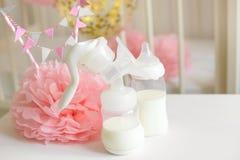 Μπουκάλια αντλιών στηθών και μωρών με το γάλα, το διάφορα εορταστικά ντεκόρ εγγράφου και τα μπαλόνια μπροστά από την κρεβατοκάμαρ Στοκ Εικόνα
