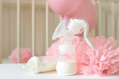 Μπουκάλια αντλιών στηθών και μωρών με το γάλα, το διάφορα εορταστικά ντεκόρ εγγράφου και τα μπαλόνια μπροστά από την κρεβατοκάμαρ Στοκ εικόνα με δικαίωμα ελεύθερης χρήσης