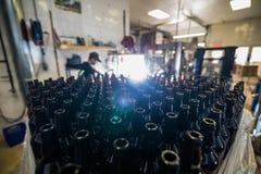 Μπουκάλια γυαλιού που συσσωρεύονται για την πλήρωση Στοκ Φωτογραφίες