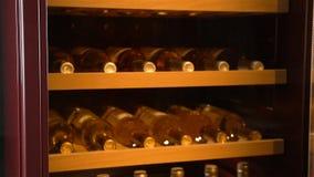Μπουκάλια κρασιού κινηματογραφήσεων σε πρώτο πλάνο που αποθηκεύονται στη ρυθμίζοντας υγρασία αέρα γραφείου απόθεμα βίντεο