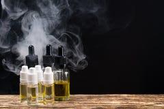 Μπουκάλια με τα ευώδη υγρά για ένα ηλεκτρονικό τσιγάρο σε ένα μαύρο υπόβαθρο με το δικαίωμα Στοκ Εικόνες