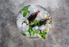 Μπουκάλια με τον ασβέστη και τη μέντα στο συντριμμένο πάγο Τοπ όψη στοκ εικόνες