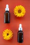 Μπουκάλια με το πετρέλαιο calendula λουλουδιών στο πορτοκάλι backgraund, geometri στοκ φωτογραφία με δικαίωμα ελεύθερης χρήσης