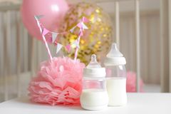 Μπουκάλια μωρών με το μητρικό γάλα με το διάφορο εορταστικό ντεκόρ εγγράφου και μπαλόνια μπροστά από την κρεβατοκάμαρα μωρών Αυτό Στοκ εικόνα με δικαίωμα ελεύθερης χρήσης
