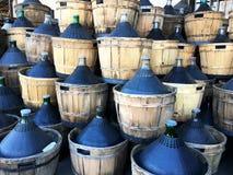 Μπουκάλια νταμιτζανών κρασιού που εσωκλείονται wickerwork έξω στο αγρόκτημα στοκ φωτογραφία με δικαίωμα ελεύθερης χρήσης