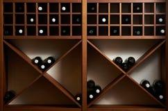 Μπουκάλια του άσπρου και κόκκινου κρασιού σε ένα ξύλινο ράφι με τα βιβλία στις δημόσιες σχέσεις στοκ εικόνες