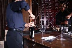 Μπουκάλι ανοίγματος ατόμων του κρασιού Στοκ εικόνα με δικαίωμα ελεύθερης χρήσης