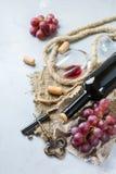 Μπουκάλι, ανοιχτήρι, ποτήρι του κόκκινου κρασιού, σταφύλια σε έναν πίνακα Στοκ εικόνες με δικαίωμα ελεύθερης χρήσης