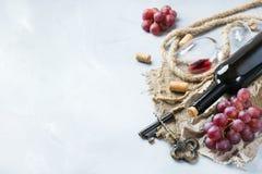 Μπουκάλι, ανοιχτήρι, ποτήρι του κόκκινου κρασιού, σταφύλια σε έναν πίνακα Στοκ Εικόνες