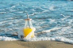 Μπουκάλι γυαλιού με τον πρόσφατα πιεσμένο τροπικό χυμό φρούτων με το άχυρο που στέκεται στην άμμο παραλιών που πλένεται από τα μπ Στοκ Φωτογραφίες
