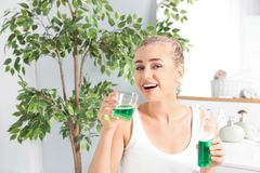Μπουκάλι και γυαλί εκμετάλλευσης γυναικών με mouthwash στο λουτρό στοκ φωτογραφία με δικαίωμα ελεύθερης χρήσης
