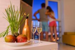 Μπουκάλι και δύο ποτήρια της σαμπάνιας στο τραπεζάκι σαλονιού στο καθιστικό, συνδέουν ερωτευμένο που αγκαλιάζεται στο υπόβαθρο κα Στοκ φωτογραφίες με δικαίωμα ελεύθερης χρήσης