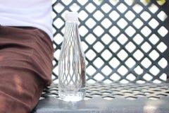 Μπουκάλι νερό που τοποθετείται σε μια καρέκλα χάλυβα εκτός από ένα άτομο που φορά το tro στοκ φωτογραφία