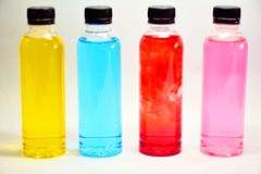 Μπουκάλι νερό των κίτρινων, μπλε, κόκκινων, ρόδινων, φωτεινών χρωμάτων Στοκ Εικόνα