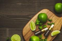 Μπουκάλι ουσιαστικού πετρελαίου Aromatherapy με τα φρούτα ασβέστη και τη μέντα φύλλων Στοκ φωτογραφία με δικαίωμα ελεύθερης χρήσης