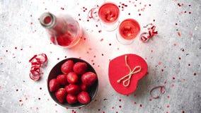 Μπουκάλι της ροδαλής σαμπάνιας, των γυαλιών με τις φρέσκες φράουλες και διαμορφωμένου του καρδιά δώρου απόθεμα βίντεο