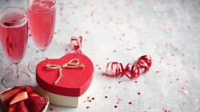Μπουκάλι της ροδαλής σαμπάνιας, των γυαλιών με τις φρέσκες φράουλες και διαμορφωμένου του καρδιά δώρου φιλμ μικρού μήκους
