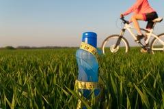 Μπουκάλι του αθλητικού νερού στάσεις μπουκαλιών στη χλόη φίλαθλος τρόπος ζωής απώλεια βάρους στοκ εικόνα