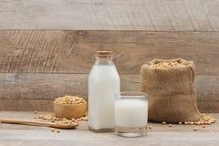 Μπουκάλι του γάλακτος και της σόγιας σόγιας στον ξύλινο πίνακα Στοκ Φωτογραφία