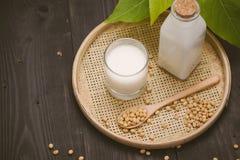 Μπουκάλι του γάλακτος και της σόγιας σόγιας στον ξύλινο πίνακα Στοκ Εικόνα
