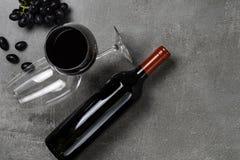 Μπουκάλι του κρασιού, goblets και των σταφυλιών στο συγκεκριμένο υπόβαθρο r στοκ εικόνα με δικαίωμα ελεύθερης χρήσης