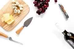 Μπουκάλι του κόκκινου κρασιού με το τυρί και του σταφυλιού aperitive στην άσπρη πλάτη Στοκ Φωτογραφία