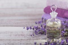 Μπουκάλι του ουσιαστικού πετρελαίου και των φρέσκων lavender λουλουδιών Στοκ Φωτογραφίες