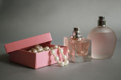 Μπουκάλια αρώματος και ρόδινο κιβώτιο με τις χάντρες μαργαριταριών σε ένα γκρίζο υπόβαθρο Στοκ φωτογραφία με δικαίωμα ελεύθερης χρήσης