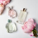 Μπουκάλια αρώματος με τα λουλούδια στο ελαφρύ υπόβαθρο Αρωματοποιία, καλλυντικά, συλλογή αρώματος Επίπεδος βάλτε Στοκ Εικόνες