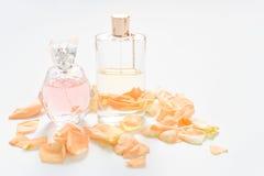 Μπουκάλια αρώματος με τα πέταλα λουλουδιών στο ελαφρύ υπόβαθρο Αρωματοποιία, συλλογή αρώματος Εξαρτήματα γυναικών Στοκ φωτογραφία με δικαίωμα ελεύθερης χρήσης